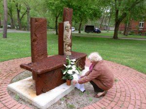 Bild:UeBV e.V. MD Frau Mortensens legt ein Gebinde am Mahnmal ab.