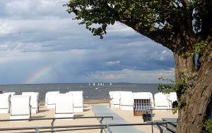 Zu sehen ist ein Ausblick auf die Strandpromenade Ueckermünde. Im Hintergrund sind weiße Strandkörbe und das Meer zu sehen.
