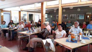 Das Bild zeigt einige Teilnehmer*innen, die an Tischen sitzen. Sie hören dem Vortrag zu im Rahmen der Veranstaltung zum 17. Forum zum Trägerübergreifenden Persönlichen Budget