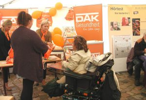 Zu sehen ist Frau Deutsch in ihrem Elektrorollstuhl. Sie spricht an einem Stand der DAK Krankenkasse mit zwei Frauen.