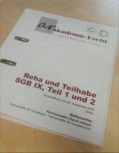 """Das Bild zeigt einen Ordner mit Seminarunterlagen zur SGB IX Fortbildung. Auf dem Ordner steht in großer Schrift """"Reha und Teilhabe, SGB IX, Teil 1 und 2""""."""