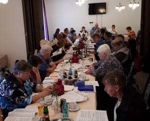 Zu sehen ist ein langer Tisch, an dem ca. 30 Mitglieder sitzen. Sie lesen in ausgeteilten Unterlagen.