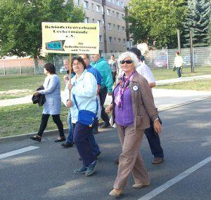 """Zu sehen sind mehrere Mitglieder des BV Ueckermünde. Sie laufen auf der Straße und halten ein Vereinsschild hoch mit der Aufschrift """"Für Selbstbestimmung und Würde"""""""