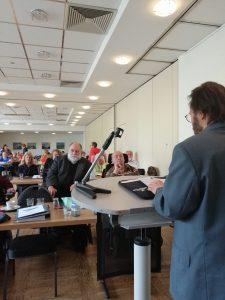 Das Bild zeigt den Referenten Hammerschmidt während seiner Rede, sowie die Mitgliederversammlung.