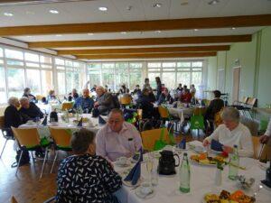 Das Bild zeigt ca. 25 Personen, die an gedeckten Tischen sitzen und sich unterhalten