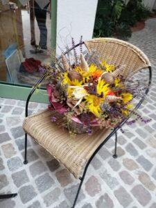 Das Bild zeigt einen Rattanstuhl, auf welchem ein buntes Blumengesteck steht.
